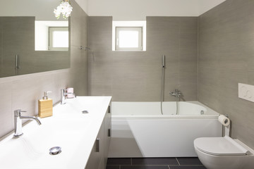 Modern bathroom with large brown tiles and large mirror