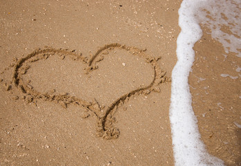 Heart drawn on the sand of the beach washed by sea wave.