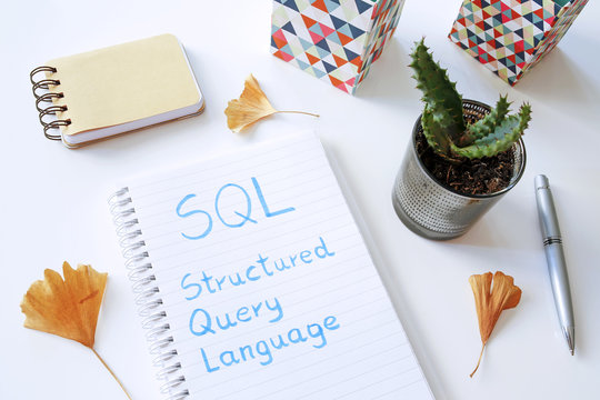 SQL Structured Query Language written in notebook on white table