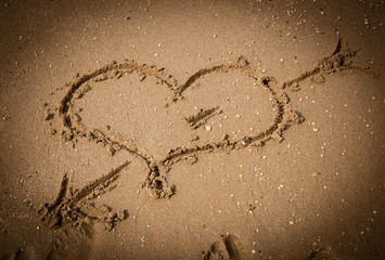 Heart pierced by arrow on the sand of the beach. Vignette.