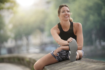 Athletic woman stretching out after running