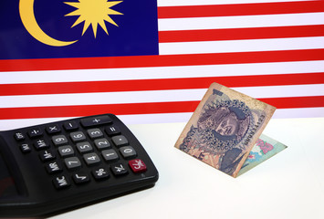 One ringgit banknote of Malaysia and calculator on the white floor with Malaysian nation flag background, the concept of finance.