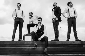 Groom and groomsmen have fun posing on the wooden stairs outside