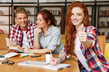 Group of smiling teenagers doing homework