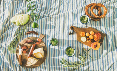 Printed kitchen splashbacks Picnic Flat-lay of summer picnic set with fruit, cheese, sausage, bagels and lemonade over striped blanket, top view