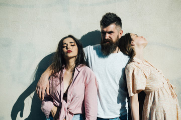 Bearded man standing with two women over white wall. Man choosing between brutal femme fatale and innocent young girl, love triangle, relationship problems concept
