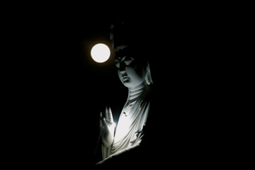 The full moon is seen behind a Buddha statue during the Vesak Day celebrations at Duoc Thuong pagoda in Hanoi