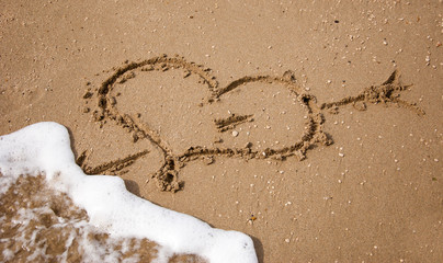 Heart pierced by arrow on the sand at the beach washed by sea wave.