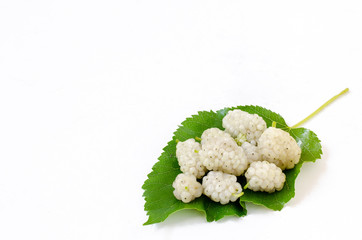Ripe white mulberries on a leaf with empty space for text