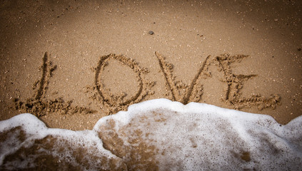 LOVE inscription on the beach sand and sea wave. Vignette.