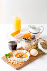 Healthy breakfast in glass mason jar with oat flakes, granola, milk, dry fruits and nuts, dates, honey, orange juice, eggs for morning fitness on wooden board platter on white background isolated