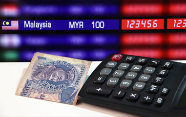 One ringgit banknote of Malaysia and calculator on the white floor with digital board of currency exchange money background, the concept of finance.
