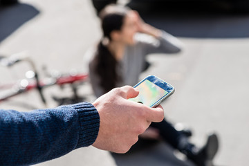 Close-up of the hand of a man calling the emergency number for helping an injured woman after bicycle accident on the street