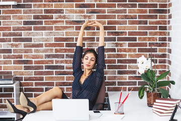 Relaxed business woman with legs on the desk in office extending