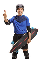 Senior with protective gear and longboard making a thumb up sign