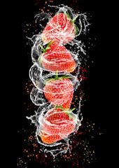 Splashing strawberries into water on black background
