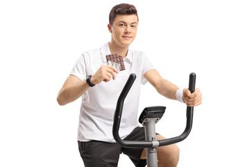 Teenage boy with a chocolate bar exercising on a stationary bike