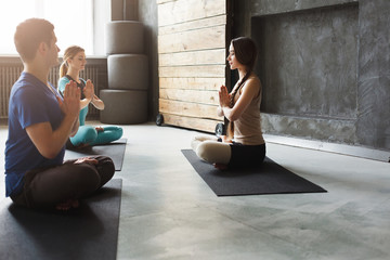Group with yoga instructor in fitness club