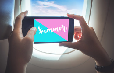 Summer time concepts with female taking a photo by smartphone on plane