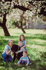 The mother,children and dog sitting on the grass