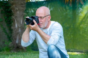 mature photographer using a camera