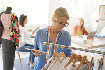Fashion designer checking handmade clothes, using tablet