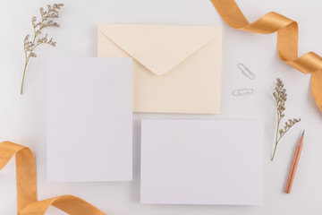 A wedding concept. Wedding Invitation, envelopes, cards Papers on white background with ribbon and decoration. Top view, flat lay, copy space