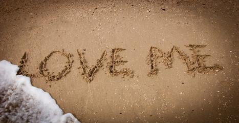 LOVE ME inscription on the beach sand and sea wave. Vignette.