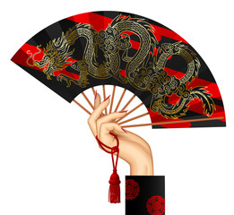 Woman's hand with a black chinese fan with gold decorative gragon isolated on white
