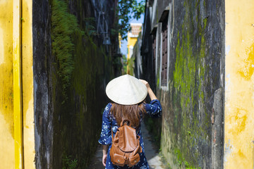 Woman tourist is wearing Vietnamese Hat (Non La) and traveling in Hoi An old town in Vietnam.