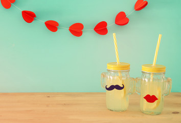 Image of fresh lemonade drink in cute cactus shape glasses wearing mustache and lips, over wooden table and hearts garland background. Tropical summer romantic vacation concept.