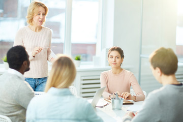 Pretty middle-aged entrepreneur wearing jeans and knitted sweater sharing her creative ideas with subordinates while having productive working meeting at boardroom