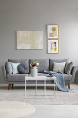 Real photo of a grey couch with cushions and blanket standing in living room interior in front of a wall with paintings and behind a white table