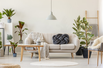 Wooden table in front of beige sofa in floral living room interior with plants. Real photo