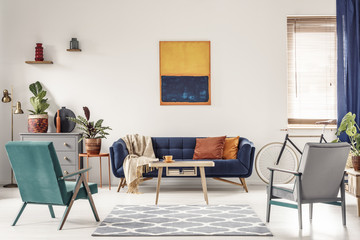 Real photo of a navy blue sofa with orange cushions and an artwork above in bright and spacious living room interior with two retro armchairs