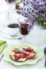 Pancakes with fresh strawberries and banana.