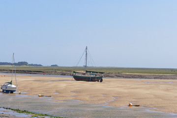 Old yacht on a sandbank at low tide