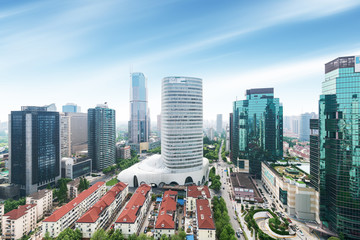 Aerial view of Shanghai's high density central business area. High rise office buildings and skyscrapers with glass surface. Urban roads with multiple lanes and green city park. Shanghai, China