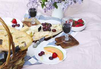Summer picnic with cheese, wine, fruits and bread.