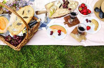 Foto op Canvas Picknick Summer picnic with cheese, wine, fruits and bread.
