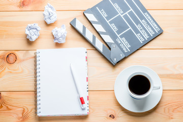 a notebook, a cup of coffee and a clapper for shooting movie episodes on wooden boards