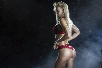 Beautiful wet sporty big tits tanned blonde girl wearing red underwear posing sideways in scenic smoke and fog under falling water drops of rain on black