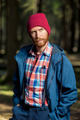 stylish man with beard in hat and jacket posing in forest