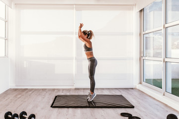 young caucasian woman doing fitness on mat at home