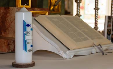 Taufkerzen mit Arrangement und Bibel. Weiße Taufkerzen für besondere Anlässe in der Kirche.