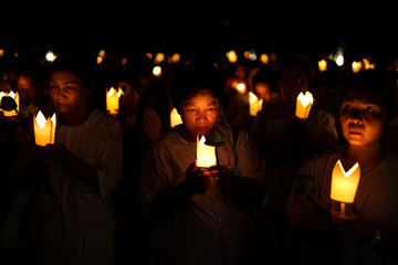 Buddhists carry candles as they pray during the Vesak Day, an annual celebration of Buddha's birth, enlightenment and death, at a temple in Chonburi province