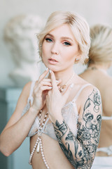 Charges of the bride in a beautiful linen dress and boudoir in the Studio. Sexy girl in a shirt with a naked body. Hair and makeup for the bride. Pre-wedding photo shoot