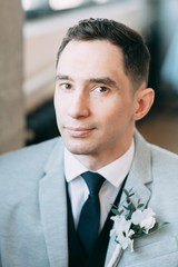 Gathering of a beautiful groom, waiting for the bride. Photo shoot in the interior Studio. Wedding in European style. Handsome man in a jacket and trousers