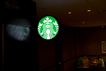 Patrons share coffee behind a reflected Starbucks logo, before more than 8,000 branches nationwide will close this afternoon for anti-bias training, in Philadelphia, Pennsylvania