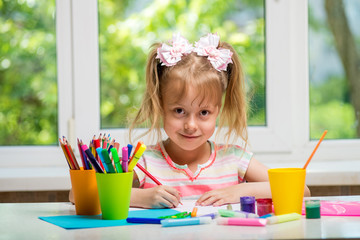 Little girl drawing paints and crayons to a room with a window.